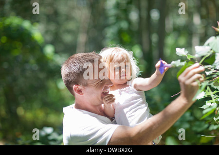 Father with baby girl plucking flowers in forest - Stock Photo