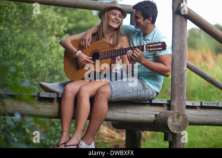 Teenage couple playing guitar and singing - Stock Photo