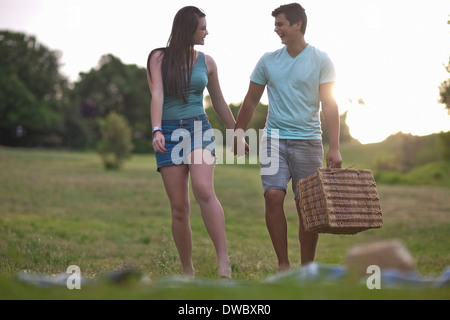 Teenage couple going for picnic in forest - Stock Photo