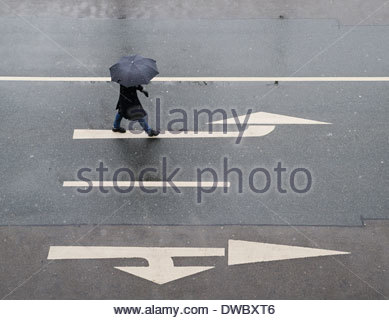 High angle view of woman with umbrella walking on road - Stock Photo