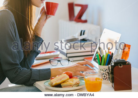 Young woman using laptop while breakfasting - Stock Photo