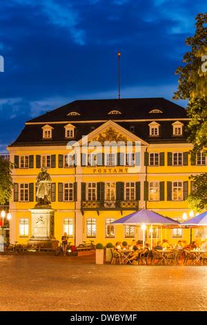 Germany, North Rhine-Westphalia, Bonn, view to Muensterplatz with street cafe at evening twilight - Stock Photo
