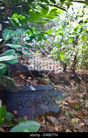 A pet cemetery in a wood, with a tree trunk tomb stone with pets' name inscribed. - Stock Photo