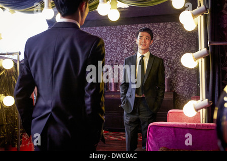 Young male client trying on new suit in traditional tailors shop - Stock Photo