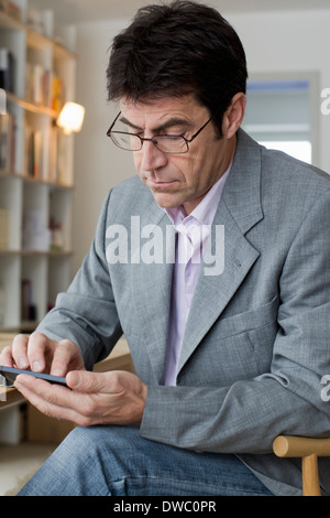 Mature man working at home texting on mobile phone - Stock Photo