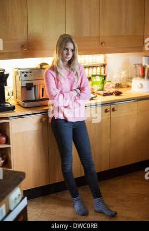 Full length of sad teenage girl standing in kitchen - Stock Photo