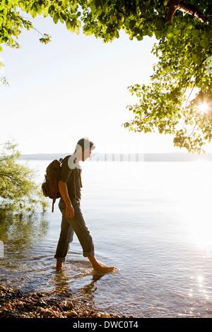 Mature man paddling in Lake Starnberg, Bavaria, Germany - Stock Photo