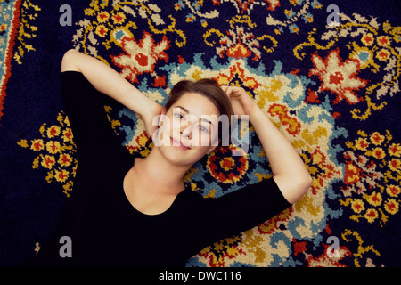 Portrait of young woman lying on patterned rug