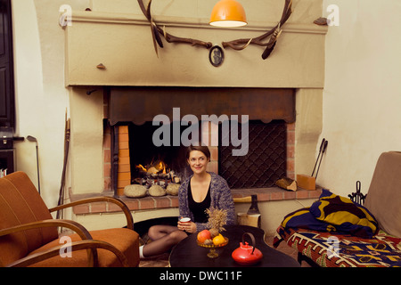 Portrait of young woman sitting on floor next to fireplace - Stock Photo