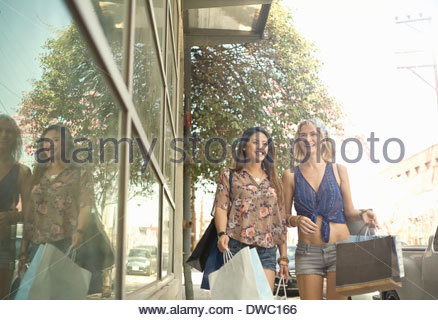 Two young women walking down street with shopping bags - Stock Photo