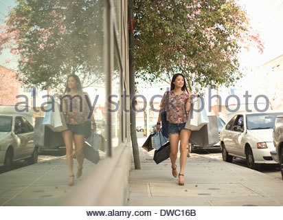 Young woman walking down street with shopping bags - Stock Photo