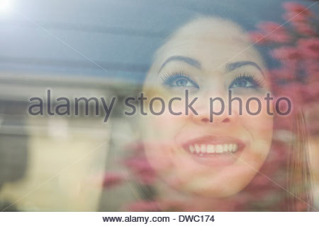 Close up portrait of young woman looking out of car window - Stock Photo
