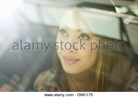 Close up of young woman looking out of car window - Stock Photo
