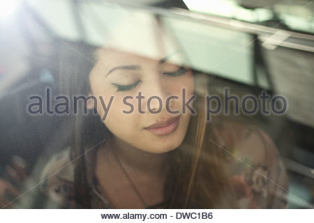 Close up of young woman in car with eyes closed - Stock Photo