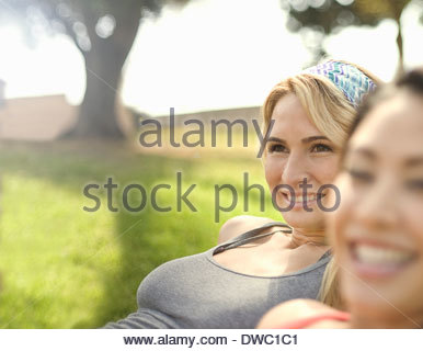 Close up of two young women enjoying sunshine in park - Stock Photo