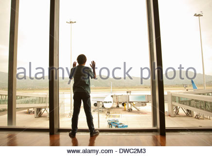 Boy looking out of window at airport - Stock Photo