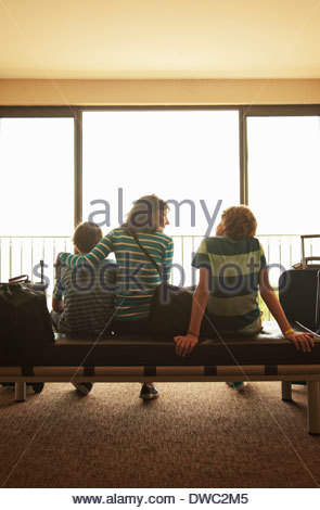 Mother and two sons in departure lounge at airport - Stock Photo