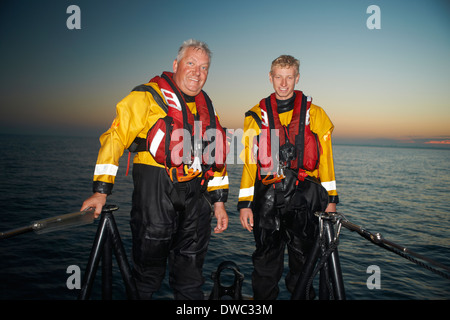 Portrait of two men crewing lifeboat at sea - Stock Photo