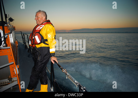 Portrait of mature man holding lifeboat railing at sea - Stock Photo
