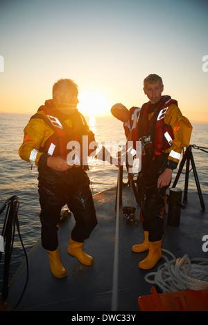 Portrait of three men holding lifeboat railing at sea - Stock Photo