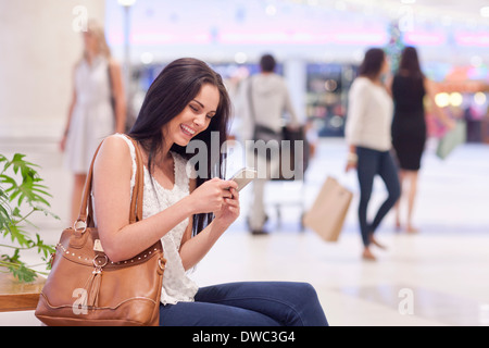 Young woman using cellular phone in mall - Stock Photo