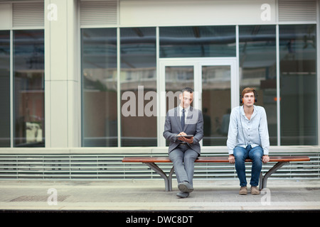 Businessman and young man sitting on train station bench - Stock Photo