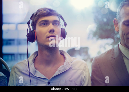 Young man daydreaming and listening to headphones on train - Stock Photo