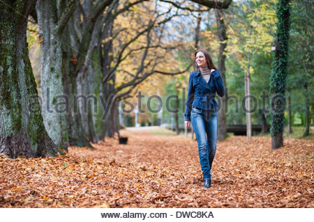 Young woman strolling through autumn leaves in park - Stock Photo