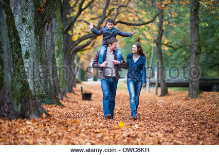 Family strolling through autumn leaves in park - Stock Photo