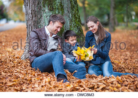 Young boy and parents sitting in park with autumn leaves - Stock Photo