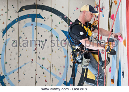 Route setter preparing new route on indoor climbing wall - Stock Photo