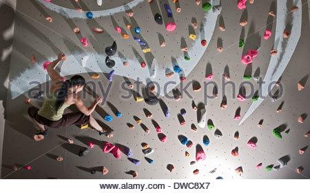 Mature woman bouldering on climbing wall - Stock Photo