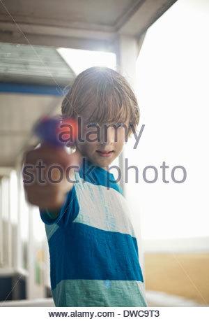 Portrait of boy holding water pistol, Southwold, Suffolk, UK - Stock Photo