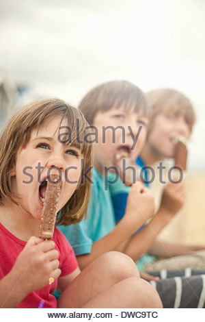 Brothers and sister enjoying ice lollies, Southwold, Suffolk, UK - Stock Photo