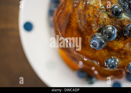 Still life overhead view of blueberry pancakes with maple syrup - Stock Photo