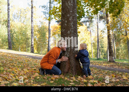 Father and son playing at bottom of tree - Stock Photo
