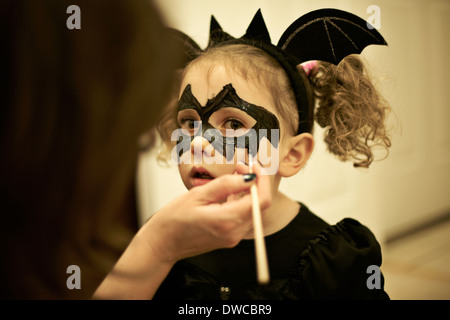 Mother painting daughters face for halloween bat costume - Stock Photo