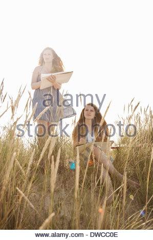 Teenage girls drawing on the beach - Stock Photo