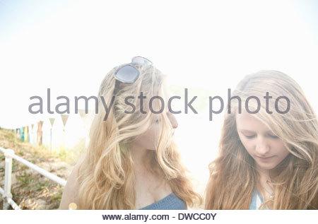 Teenage girls, beach huts in background, Southwold, Suffolk, UK - Stock Photo