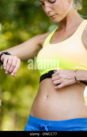Young female athlete checking heart rate monitors - Stock Photo