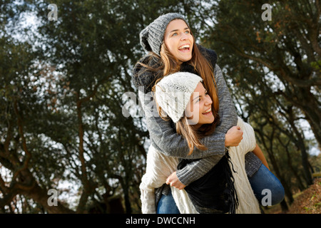 Sisters piggy back riding in forest - Stock Photo