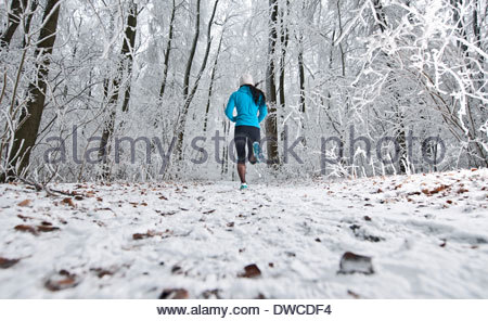 Mature woman jogging in forest in winter snow - Stock Photo