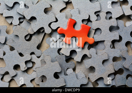 Orange puzzle piece standing out from larger group puzzle pieces. Business concept - branding, different, original. - Stock Photo