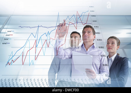 Business colleagues discussing graphs and charts seen on interactive display - Stock Photo