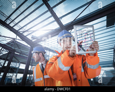 Builders working on plan details using digital tablet - Stock Photo