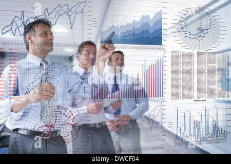 Businessmen discussing graphs and charts seen through screen - Stock Photo