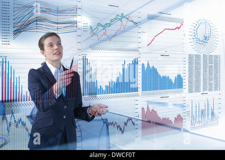Businesswoman working with graphs and charts seen through screen - Stock Photo