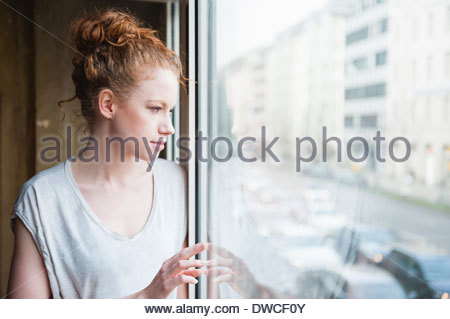 Young woman looking out of window at street - Stock Photo