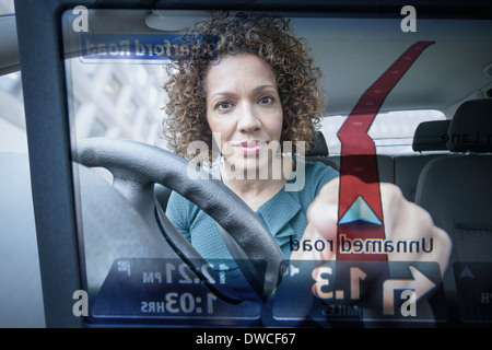 Woman operates car satellite navigation as seen through screen - Stock Photo