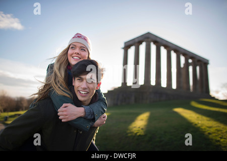 A young couple on Calton Hill with the background of the National Monument of Scotland in Edinburgh - Stock Photo